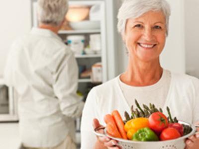 Пожилая женщина держит чашу со свежими овощами, которые богаты витаминами и минеральными веществами
