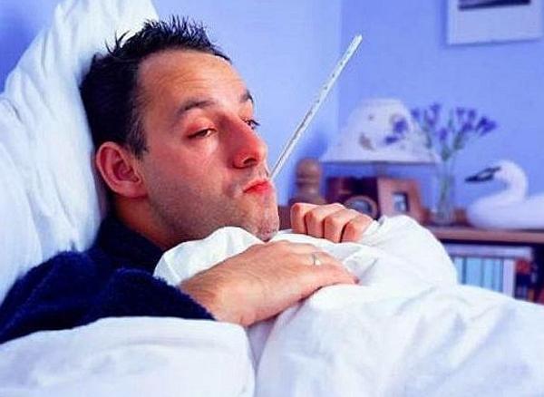 Мужчина болеет  лежа в кровати и с градусником во рту