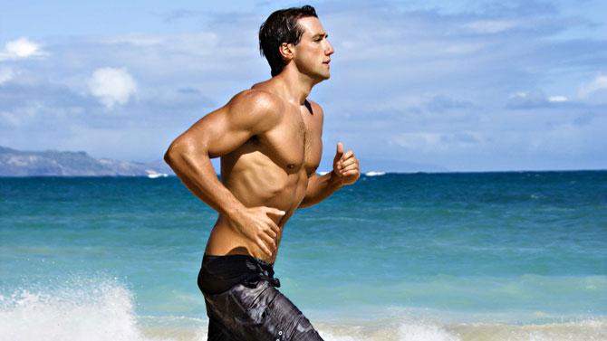 Здоровый молодой мужчина бежит вдоль берега моря
